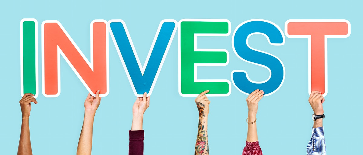 Hands holding up colorful letters forming the word invest
