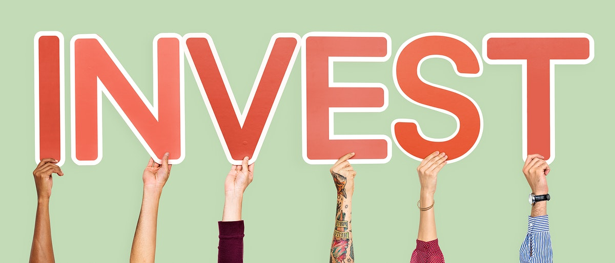 Hands holding up red letters forming the word invest