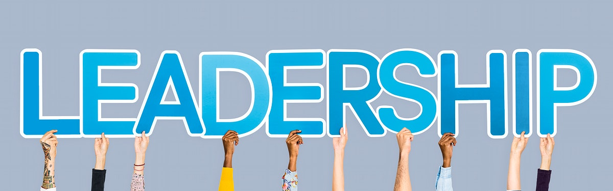 Hands holding up blue letters forming the word leadership