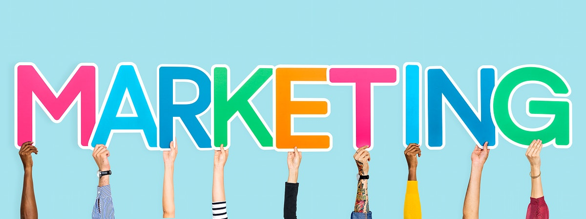 Hands holding up colorful letters forming the word marketing