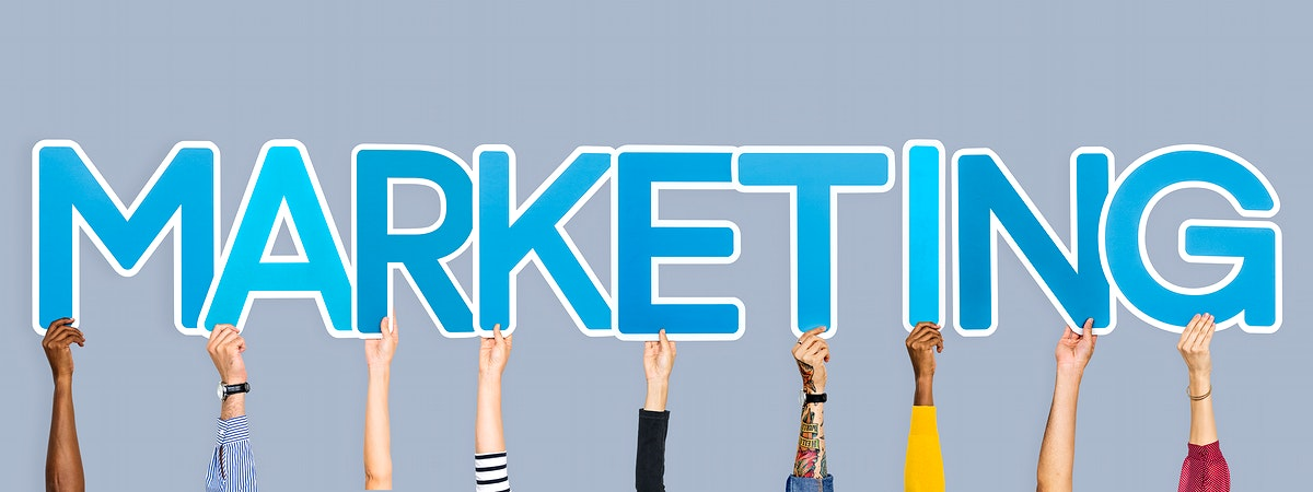 Hands holding up blue letters forming the word marketing
