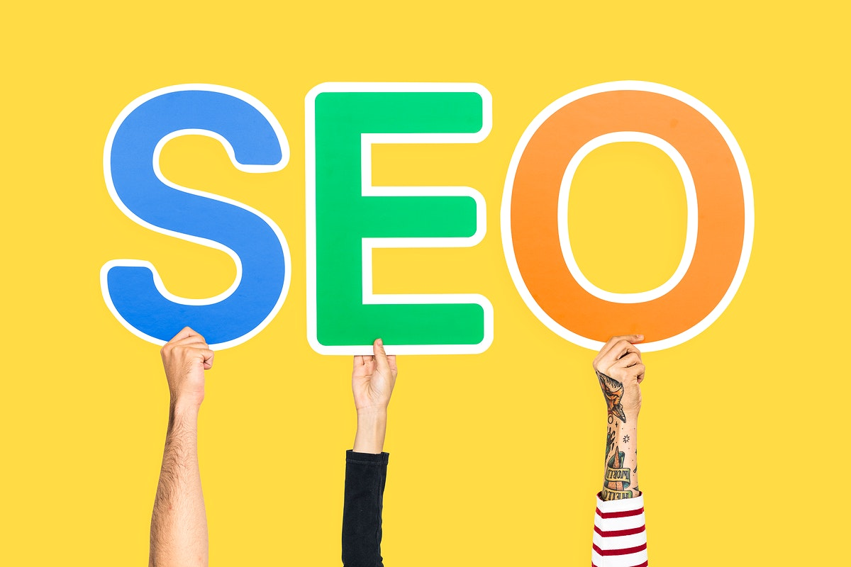 Hands holding up colorful letters forming the abbreviation  SEO