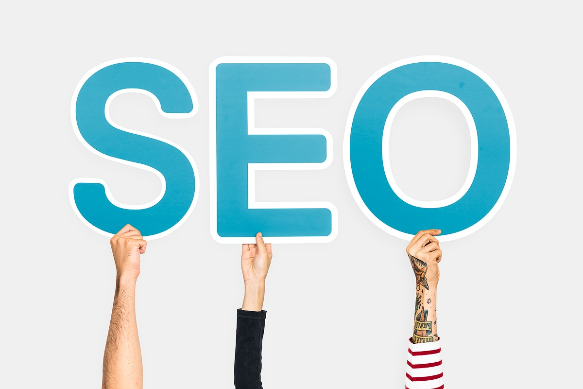 Hands holding up blue letters forming the abbreviation SEO