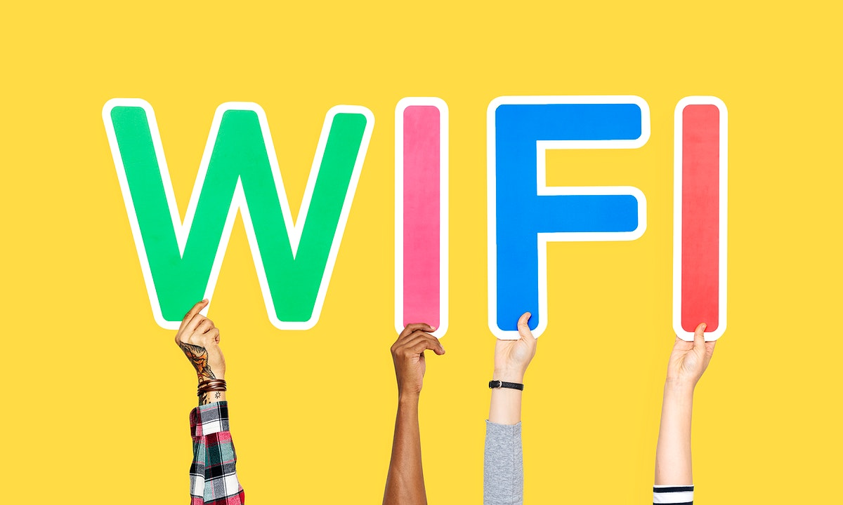 Hands holding up colorful letters forming the word wifi