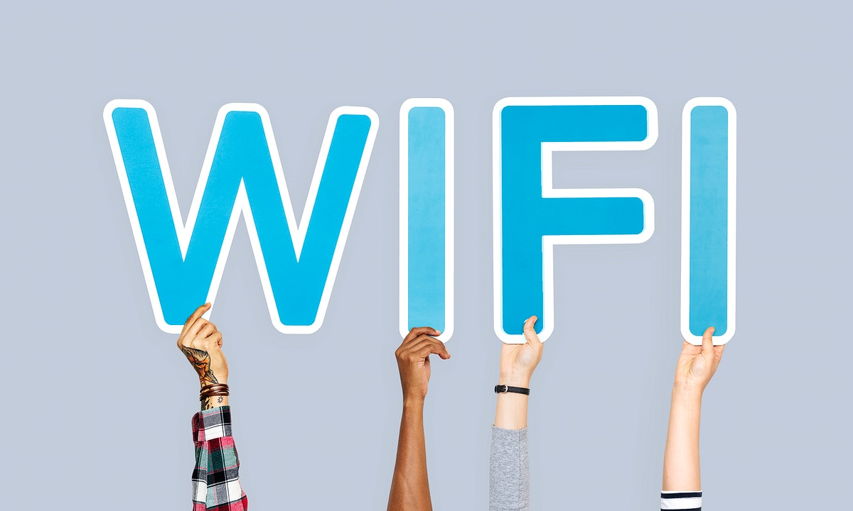 Hands holding up blue letters forming the word wifi