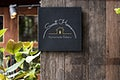 Black signage on a rustic wooden wall mockup