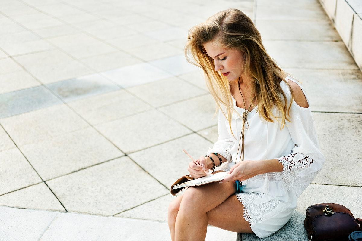 Caucasian woman sitting writing on notebook