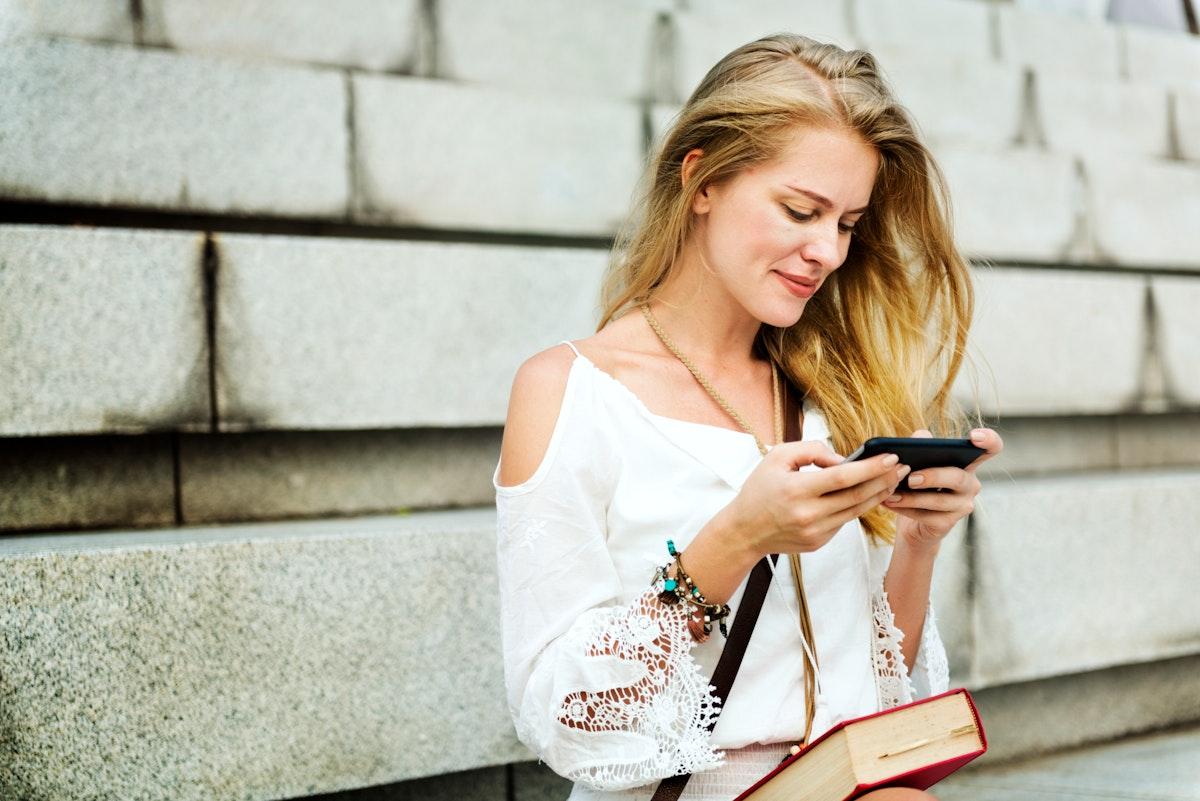 Caucasian woman using mobile phone outdoors