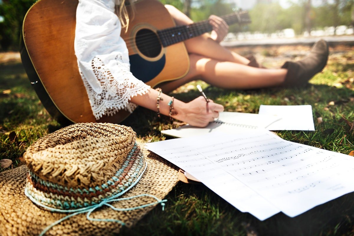 Closeup of woman guitarist sitting composing music in the park