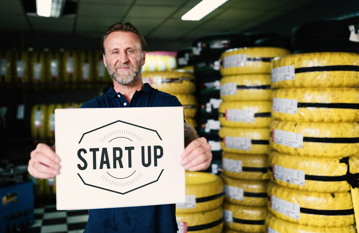 """A mechanic holding a banner that says """"Start up"""""""