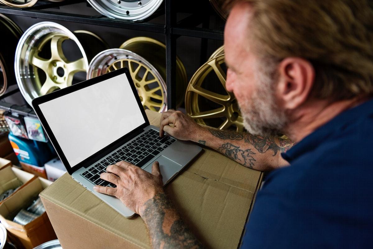 Car Parts Shop Owner Warehouse Checking Laptop Concept