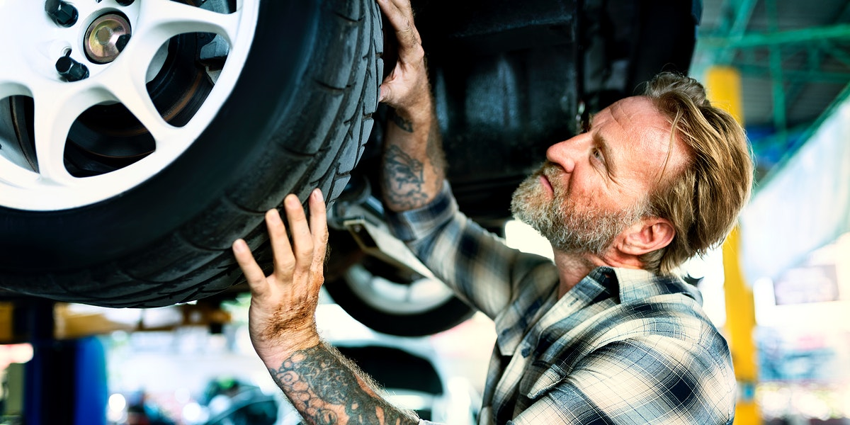 A mechanic fixing the tires of a car
