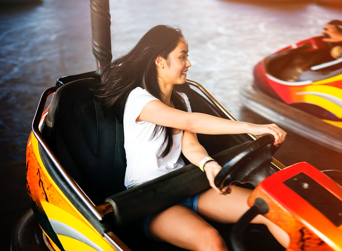 Young adult woman playing in bumper car at amusement park