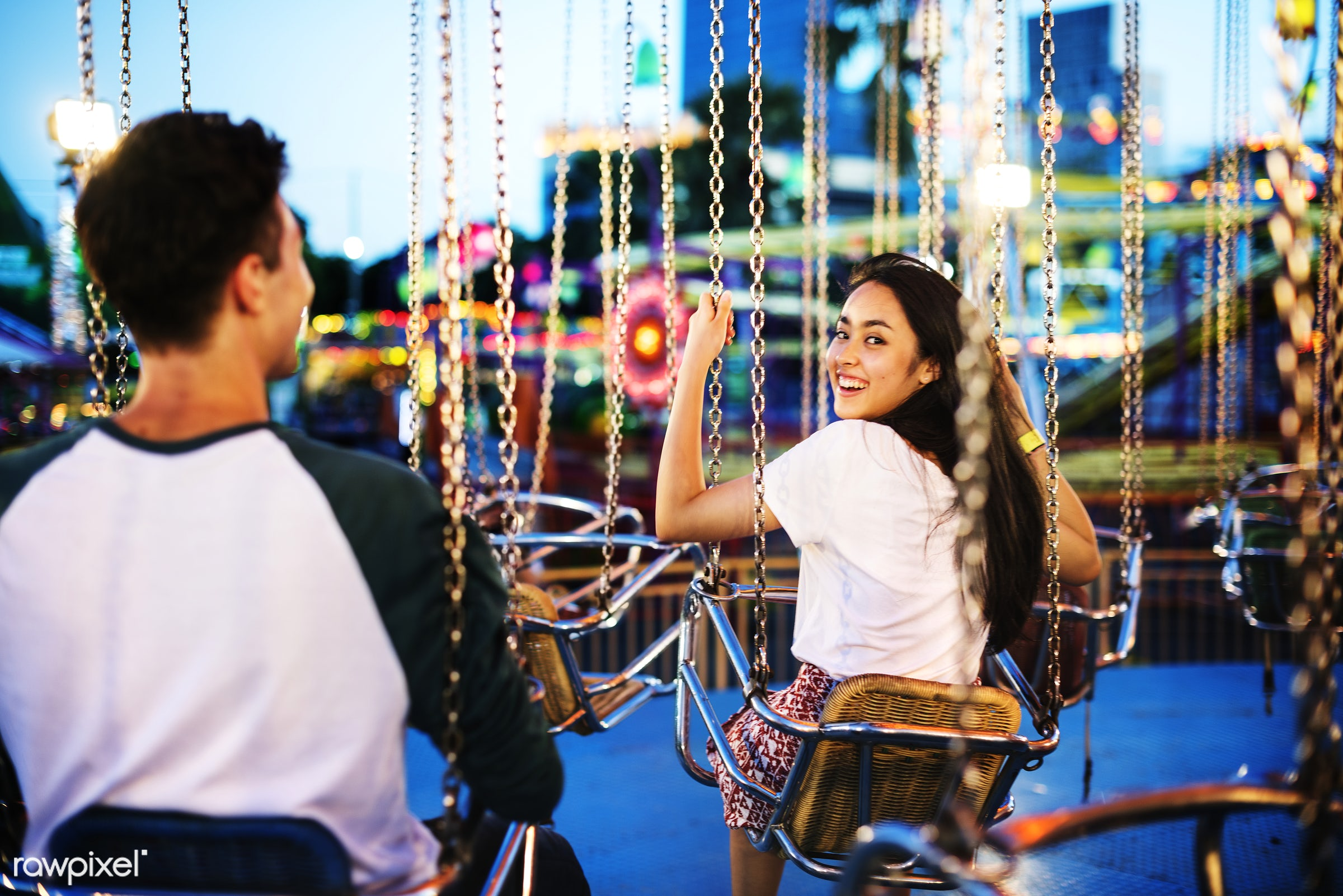 Young couple riding the swings at an amusement park - teen, girl, date, carnival, amusement park, candid, dating, indian,...
