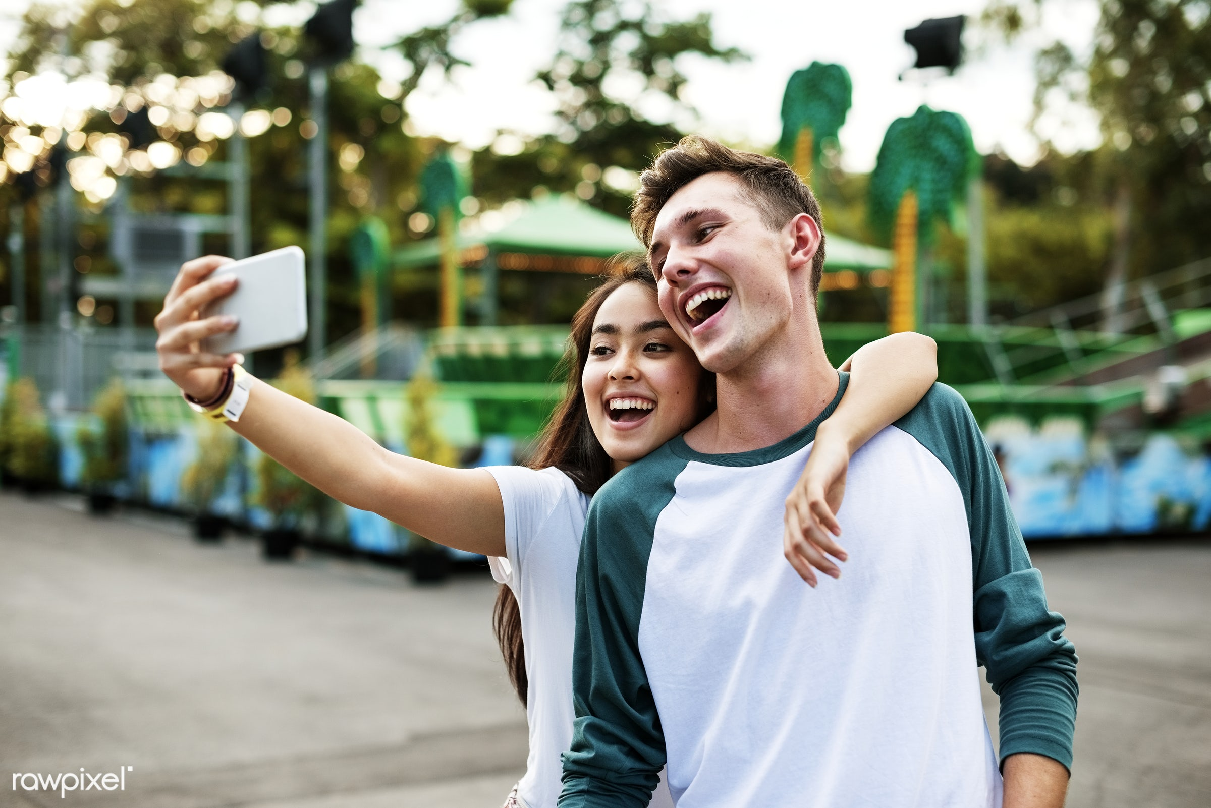 Young couple having fun together at an amusement park - teen, adorable, affectionate, american, amusement park, asian,...