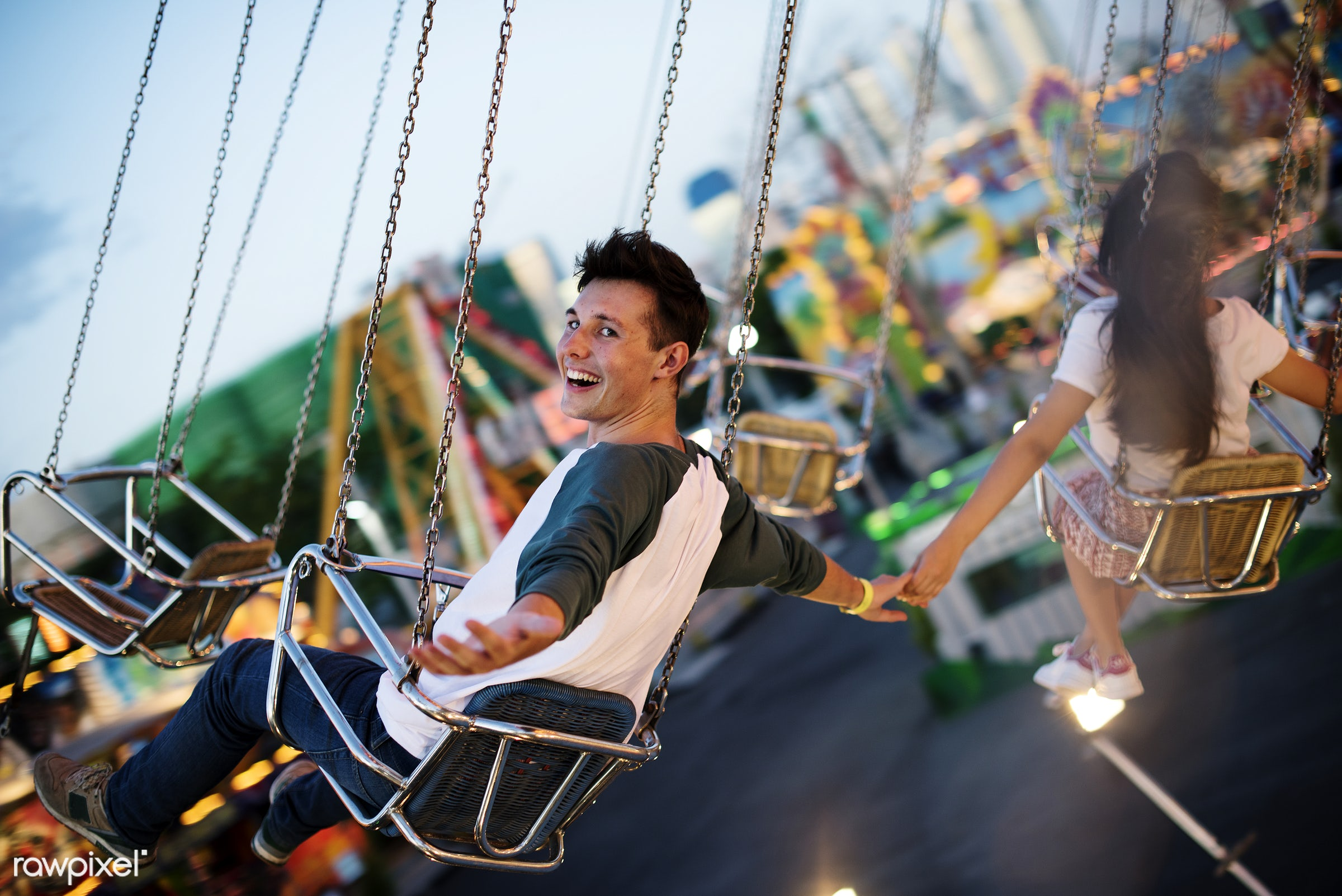 Young couple riding the swings at an amusement park - carnival, date, solo, american, amusement park, asian, back, boy,...