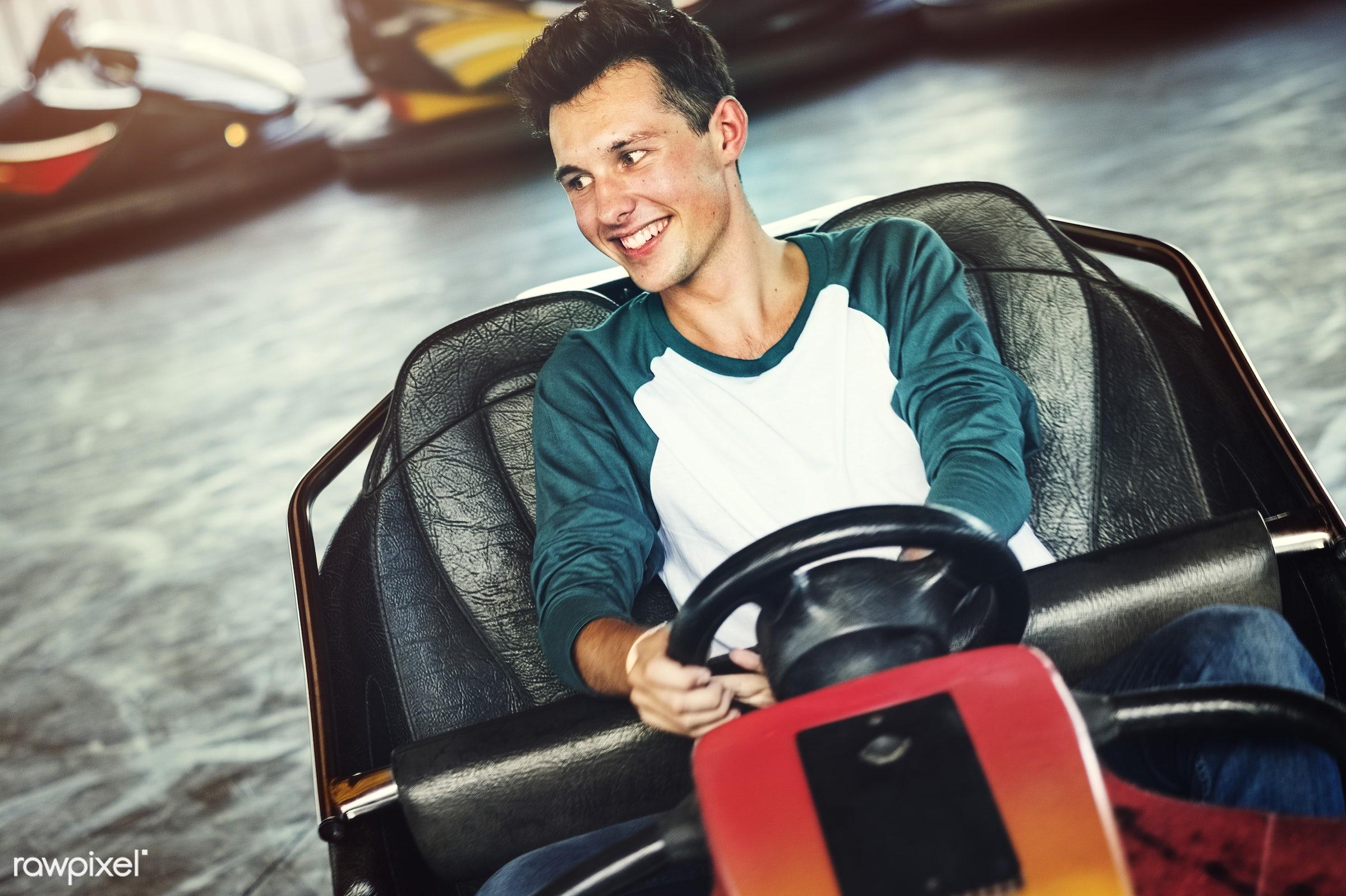 Young guy riding the bumper cars at an amusement park - adorable, affectionate, american, amusement park, beautiful,...