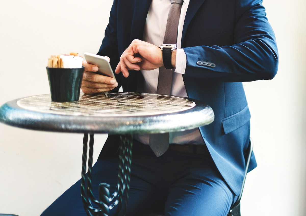 Businessman sitting checking time from wrist watch