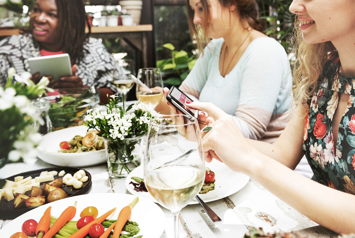 Group of diverse women having meal together using digital devices