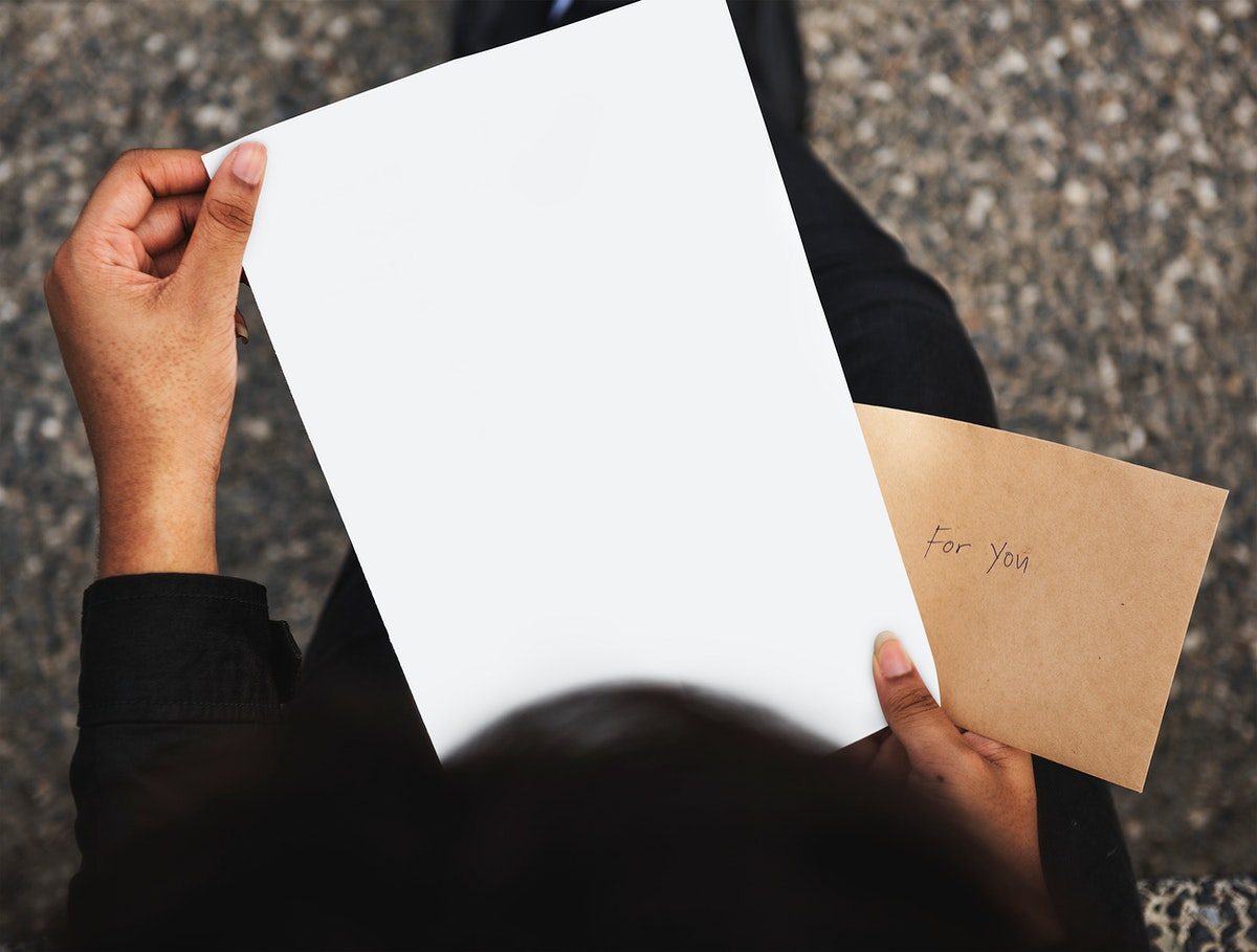 Holding a piece of blank paper mockup