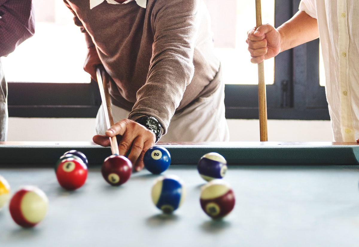 Friends playing pool game together