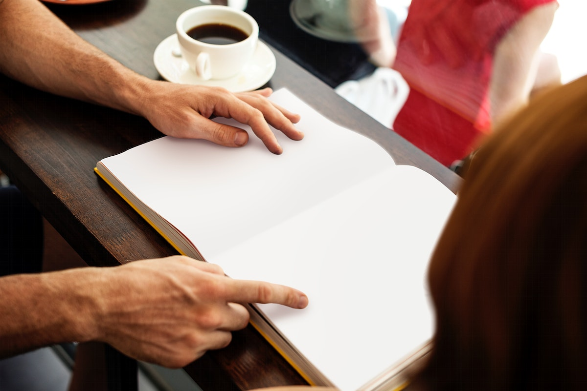 Hands pointing on blank book pages mockup