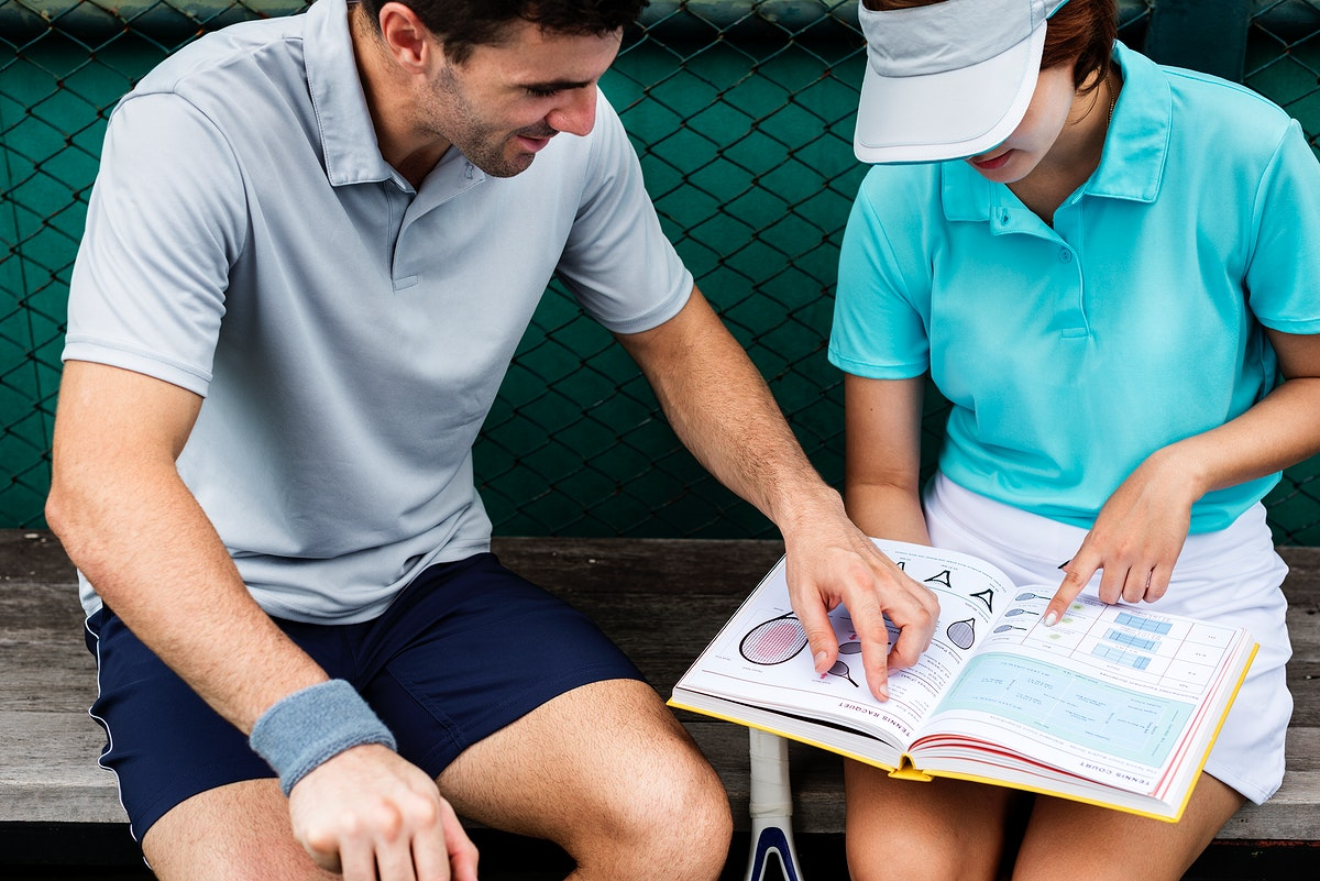 Tennis players reading a manual