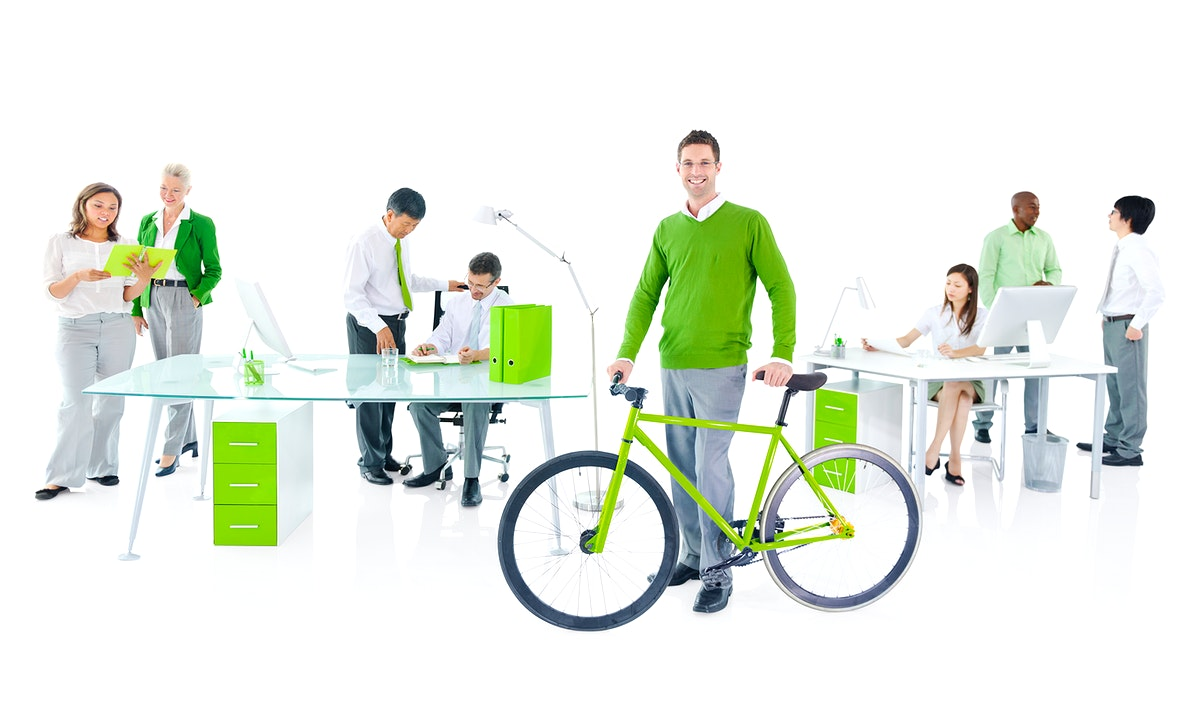 Businessman with a bicycle in a green office