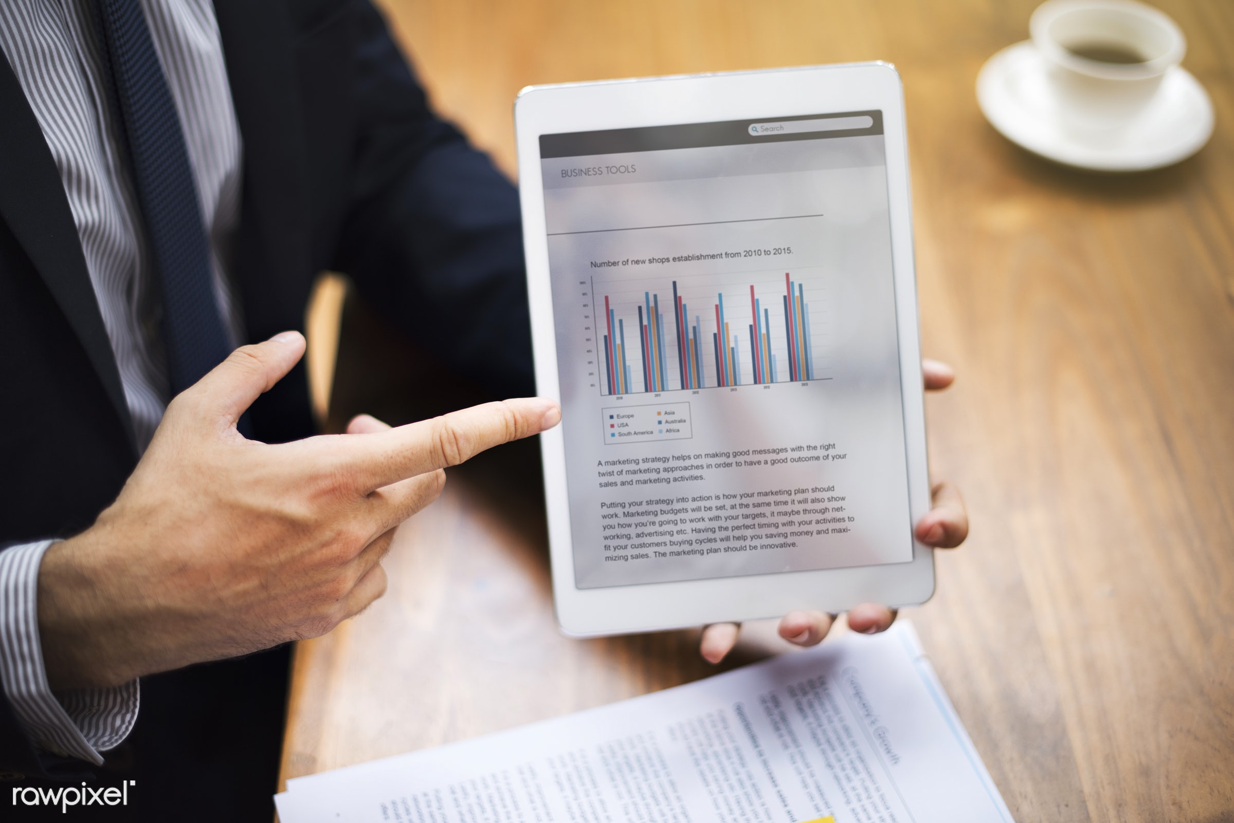 Business presentation on a tablet - analysis, analyzing, bar graph, business, business plan, businessman, coffee,...