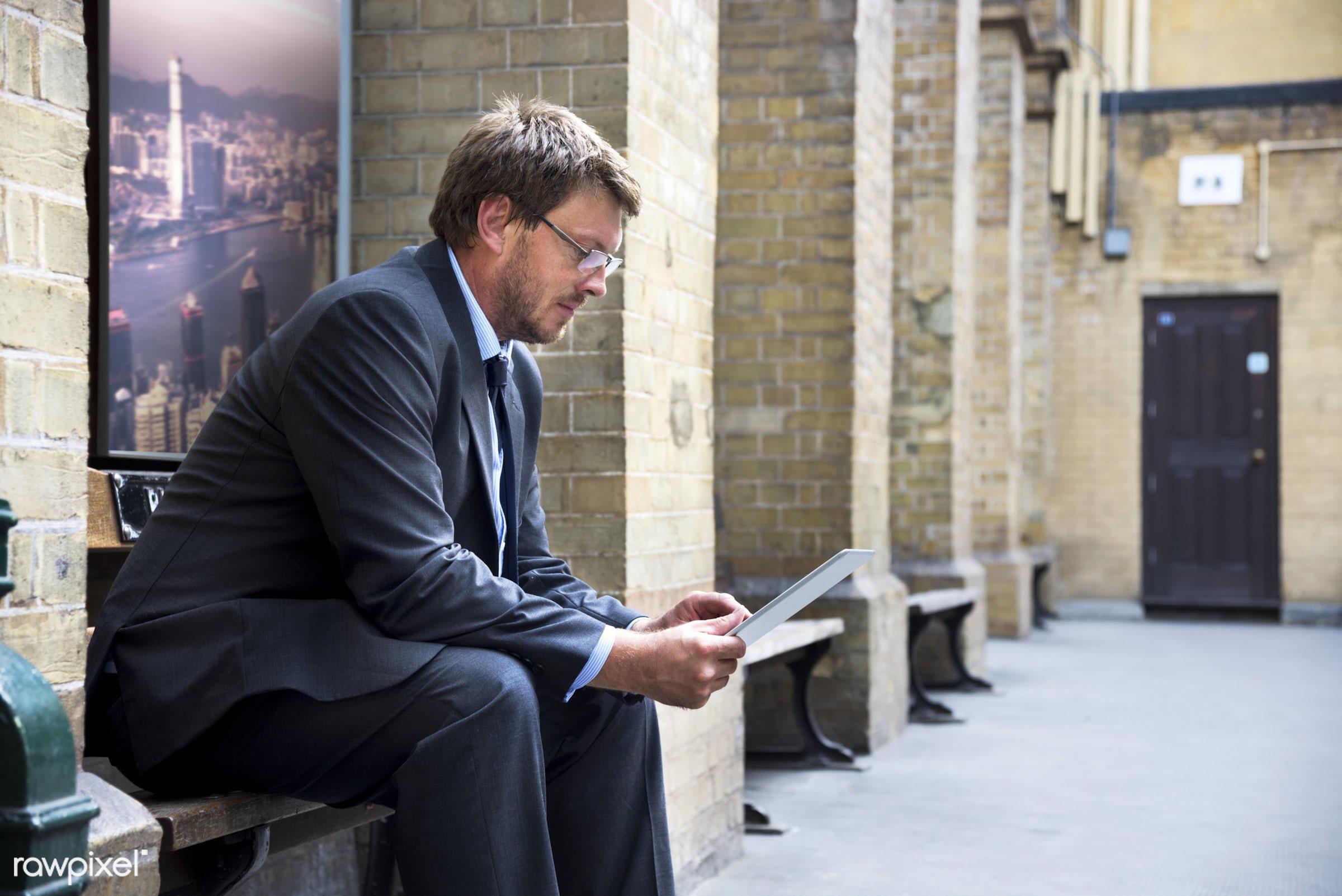 Businessman using digital tablet - adult, aspirations, bench, building, business, businessman, city, confidence, confident,...