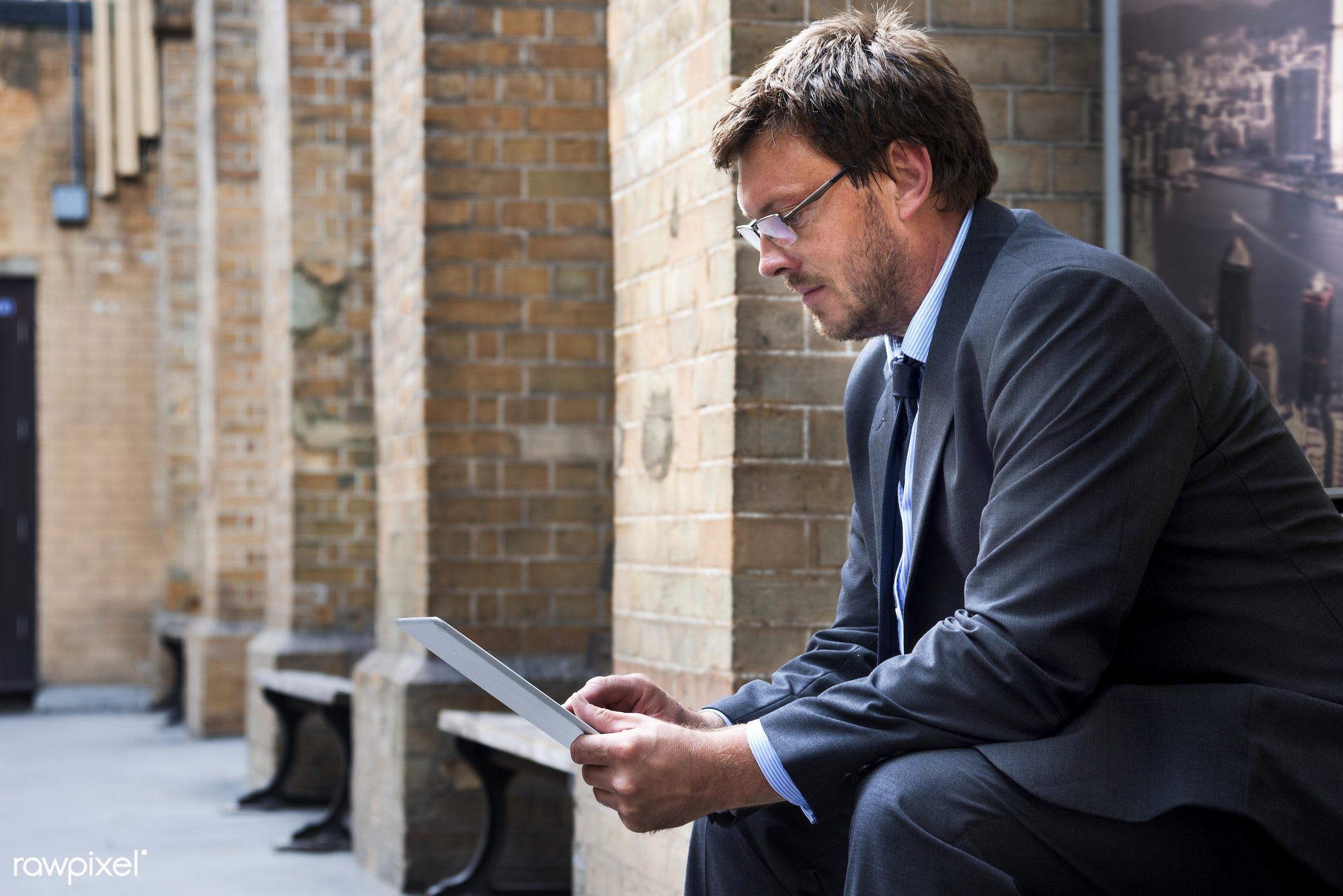 Businessman using a digital tablet - adult, aspirations, bench, building, business, businessman, city, confidence, confident...