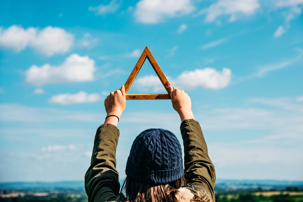 Closeup of hands holding wooden triangle frame