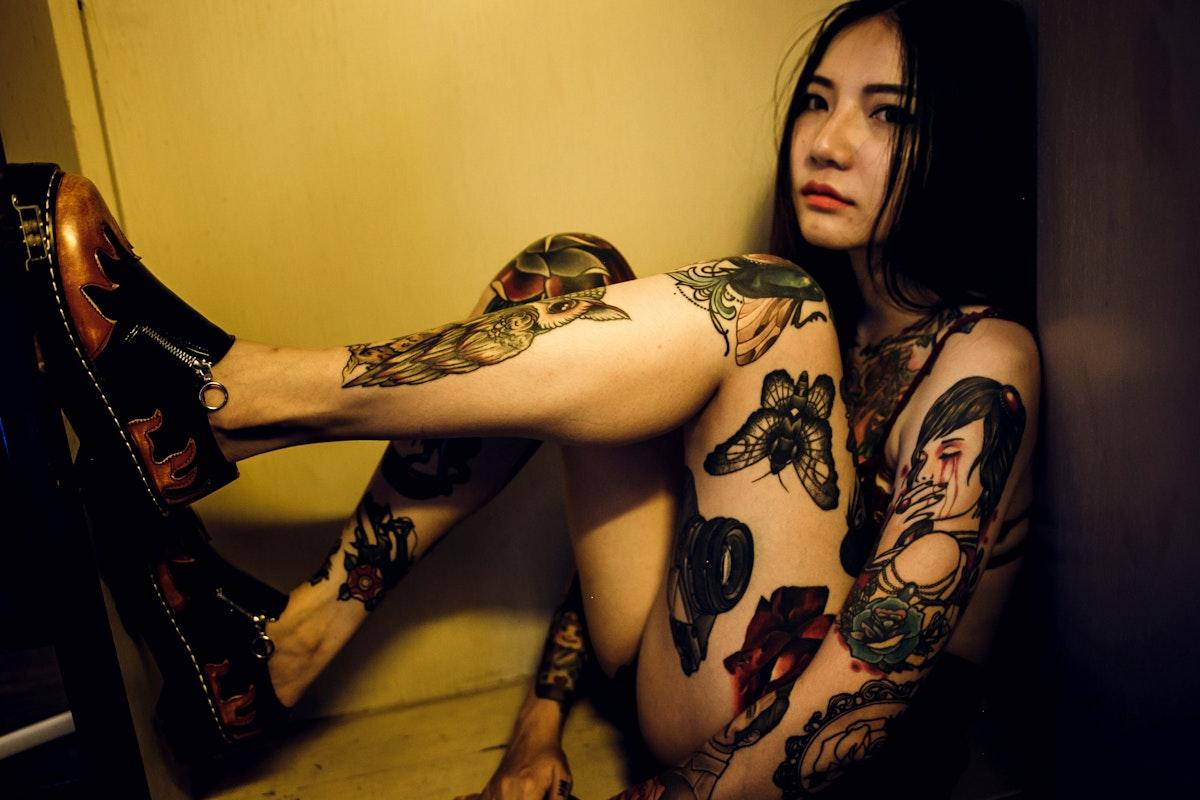 Tattooed asian woman sitting in a box