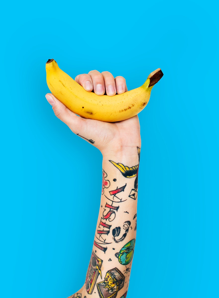 Tattoo covered arms holding a banana