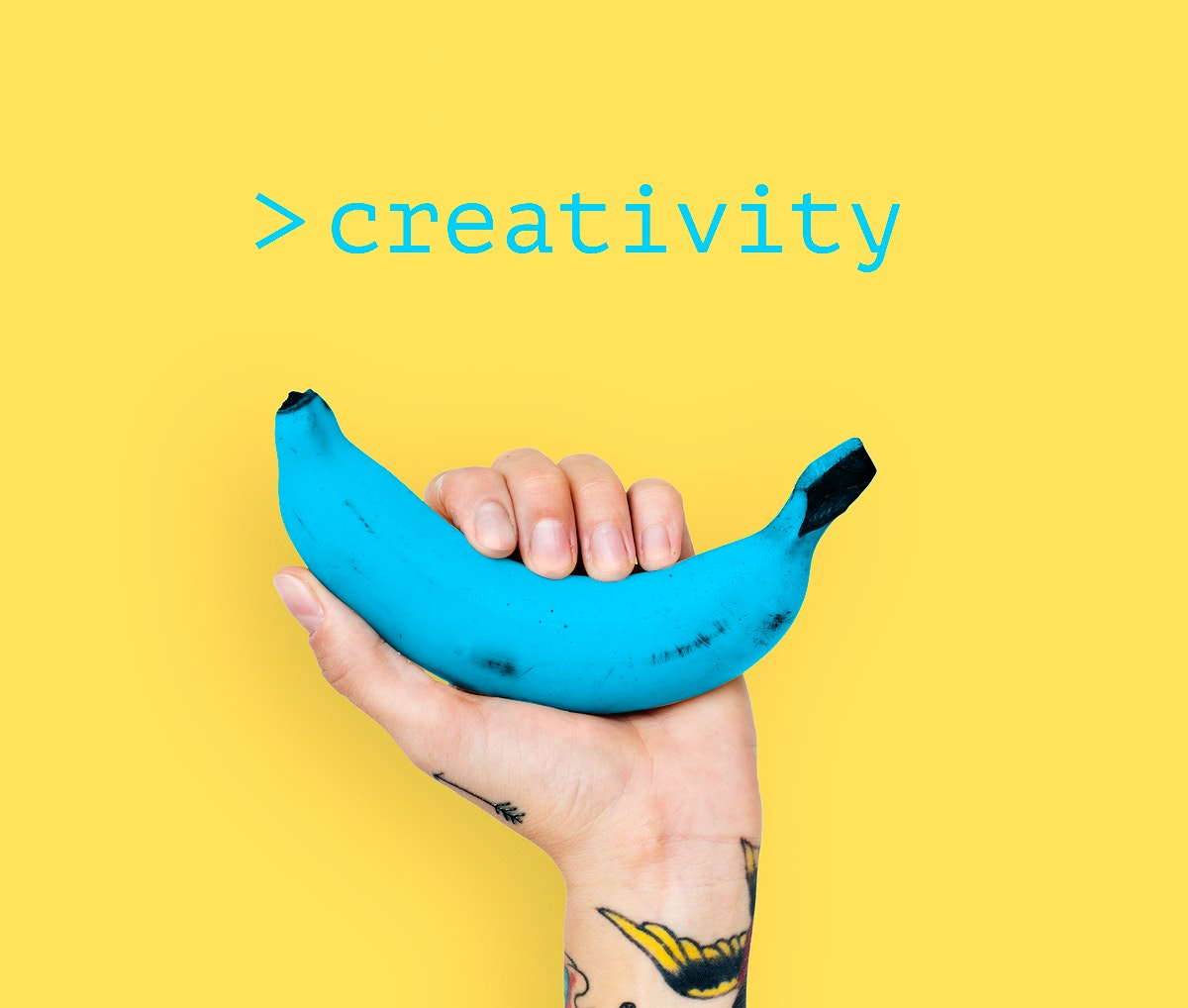 Hand with tattoo lifting blue banana with yellow background