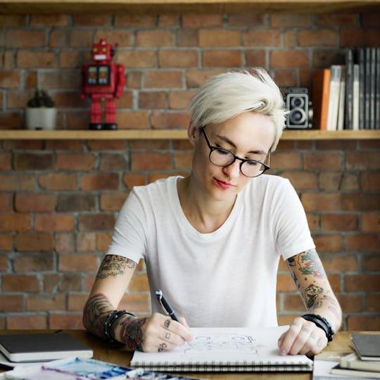 Tattooed woman drawing a sketch