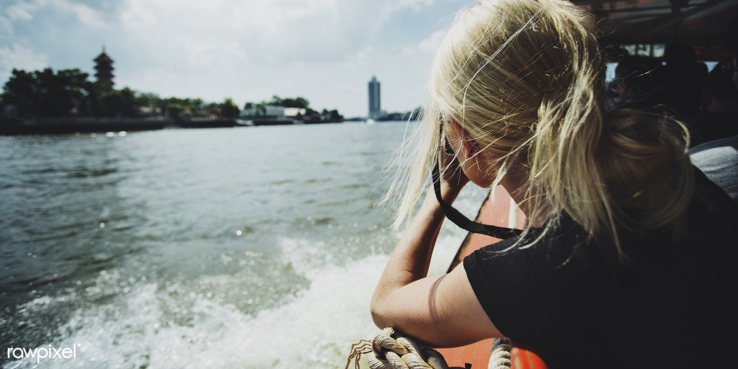 Female photographer riding a boat - woman, alone, back, blonde, boat, camera, messy hair, one, outdoors, rear, river, river...