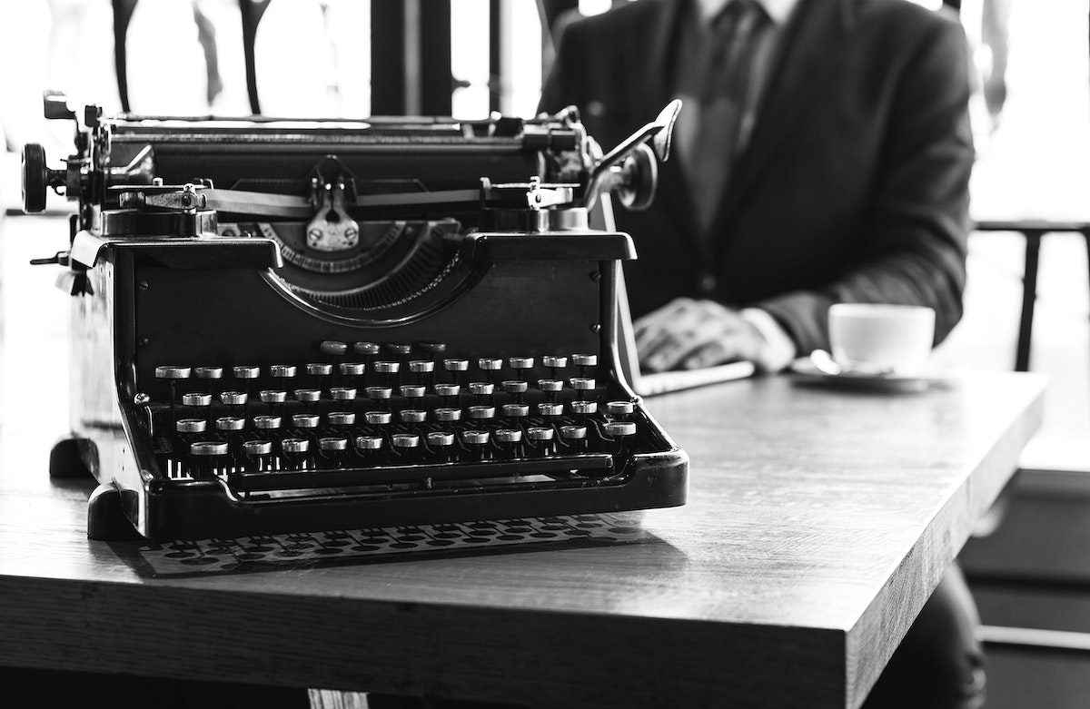 Black and white image of a vintage typewriter and a businessman