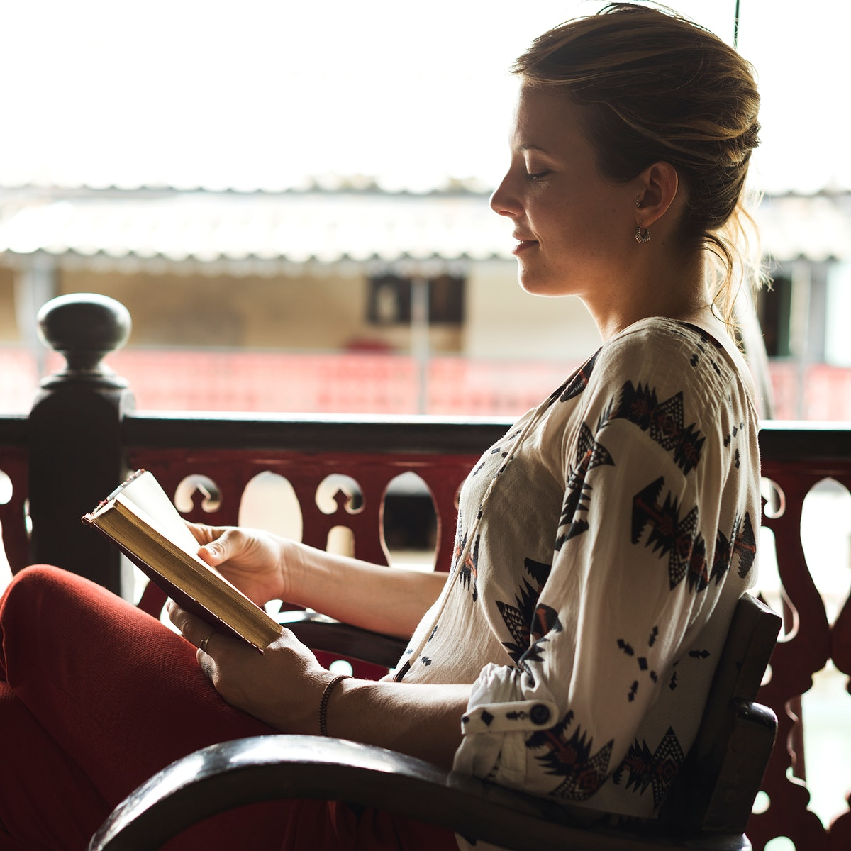 Caucasian woman reading the book at the balcony