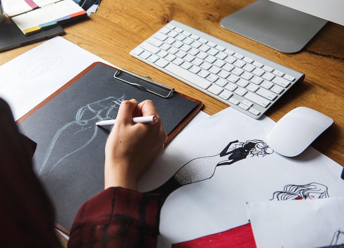 Fashion designer drawing, working in a studio