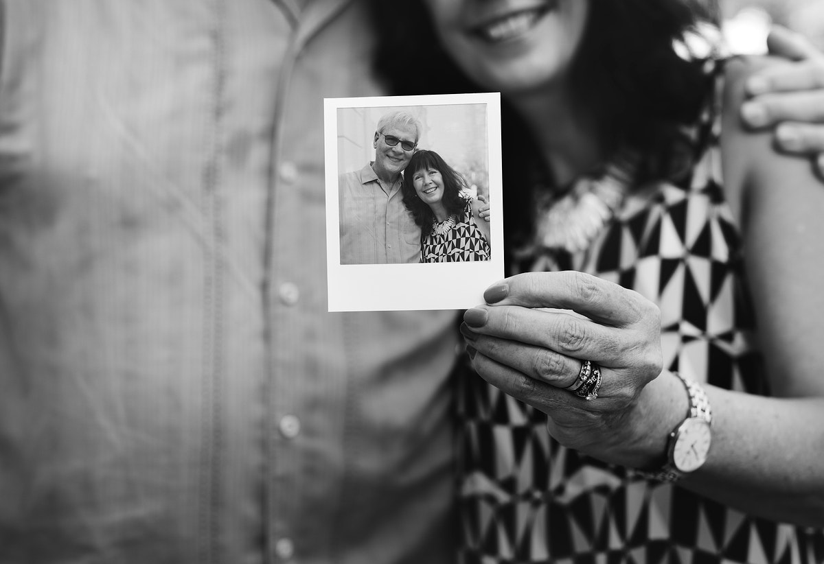 Close up couple showing instant camera image