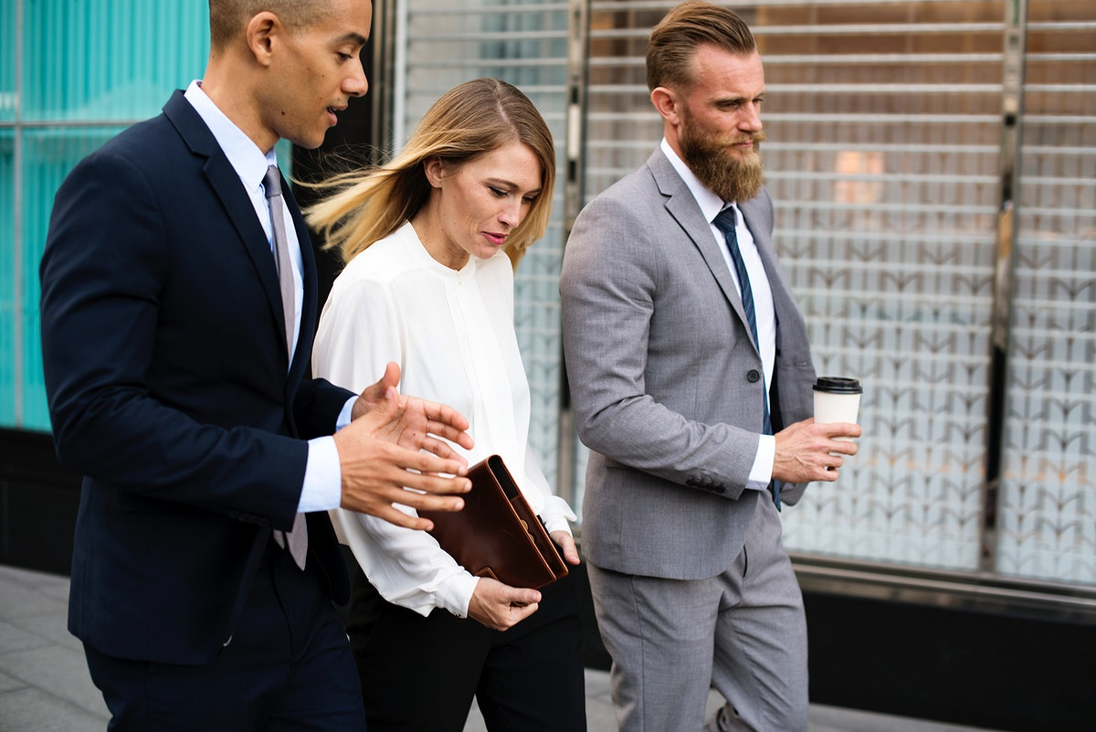 Mixed gender business people walking through the city and talking to each other