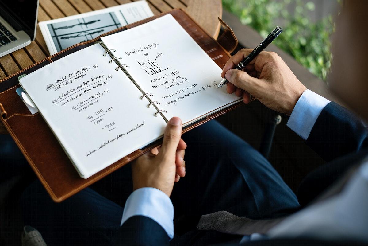 Businessman writing a business plan on a notebook