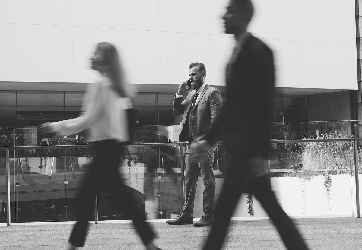 Business people walking outdoors and a businessman on the phone focused