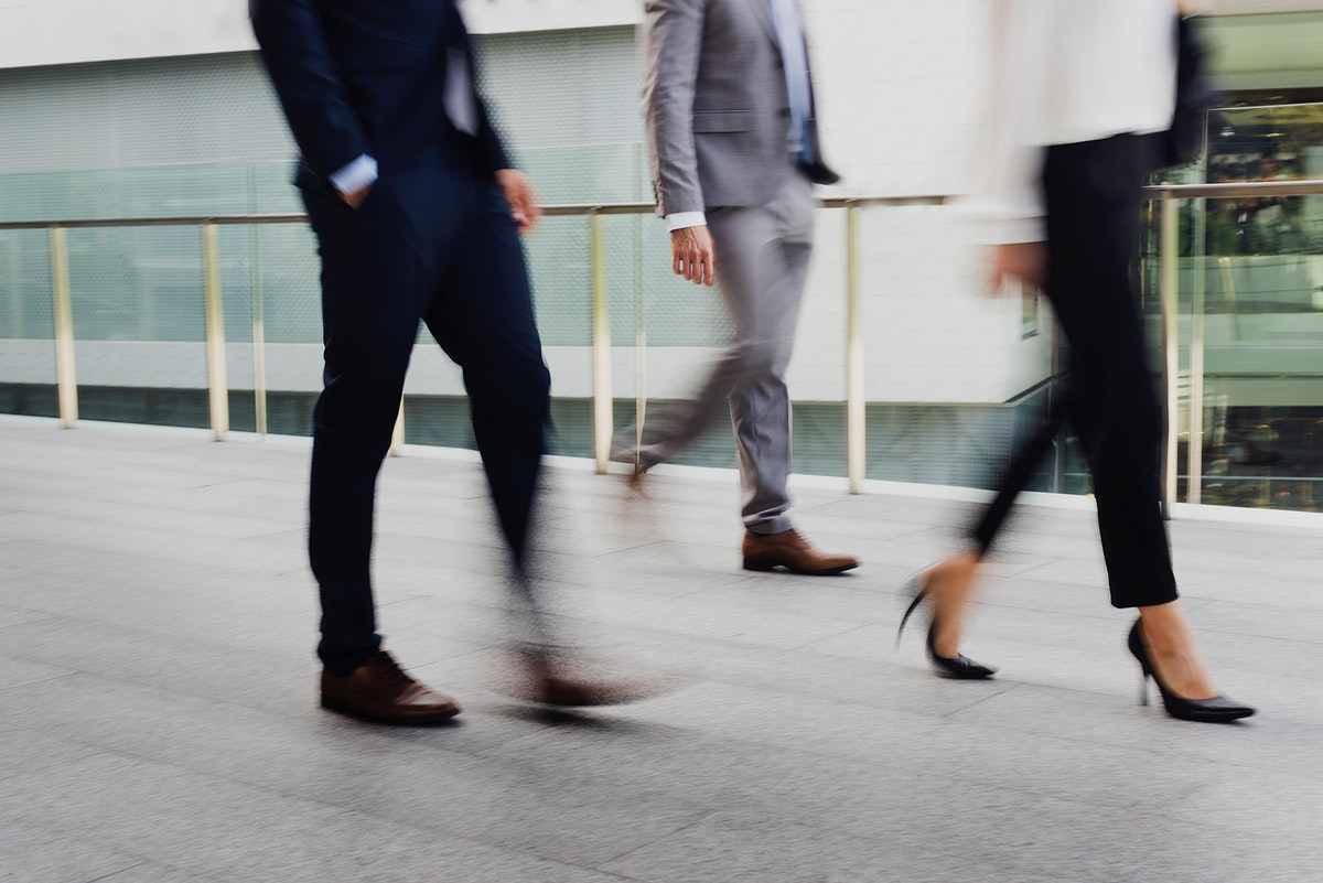 Businessmen and a businesswoman in suit walking in a city during rush hour