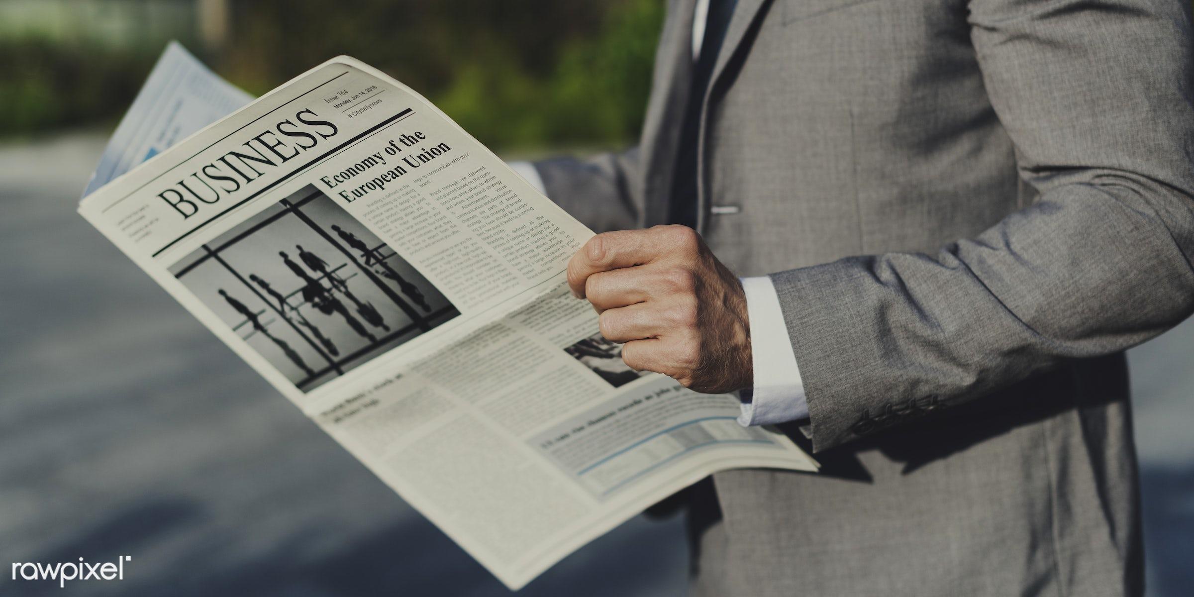 Business man reading a newspaper outdoors - accounting, adult, beard, break, business, business news, businessmen, candid,...