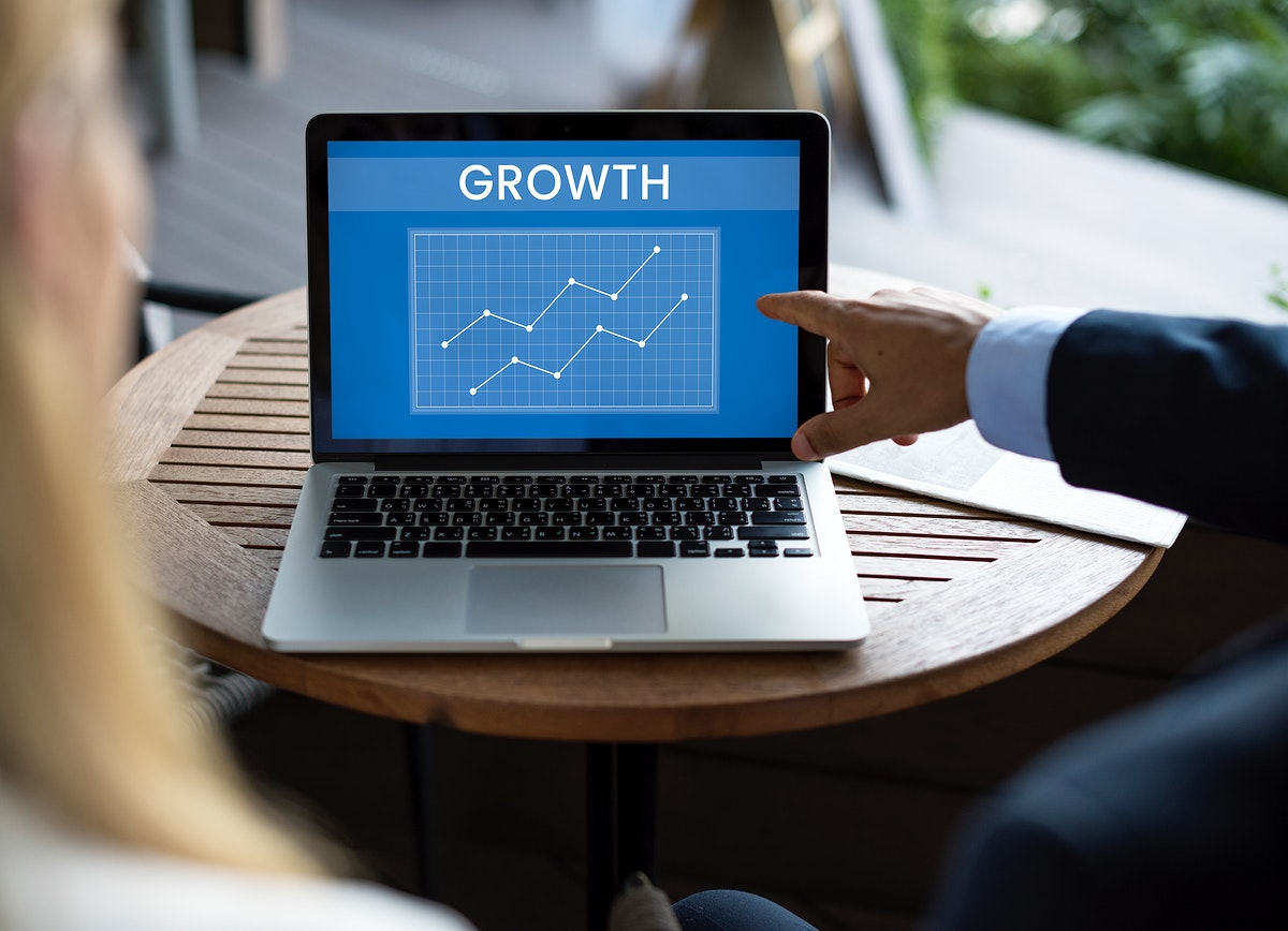 """Businessman pointing to a laptop with the word, """"GROWTH"""""""