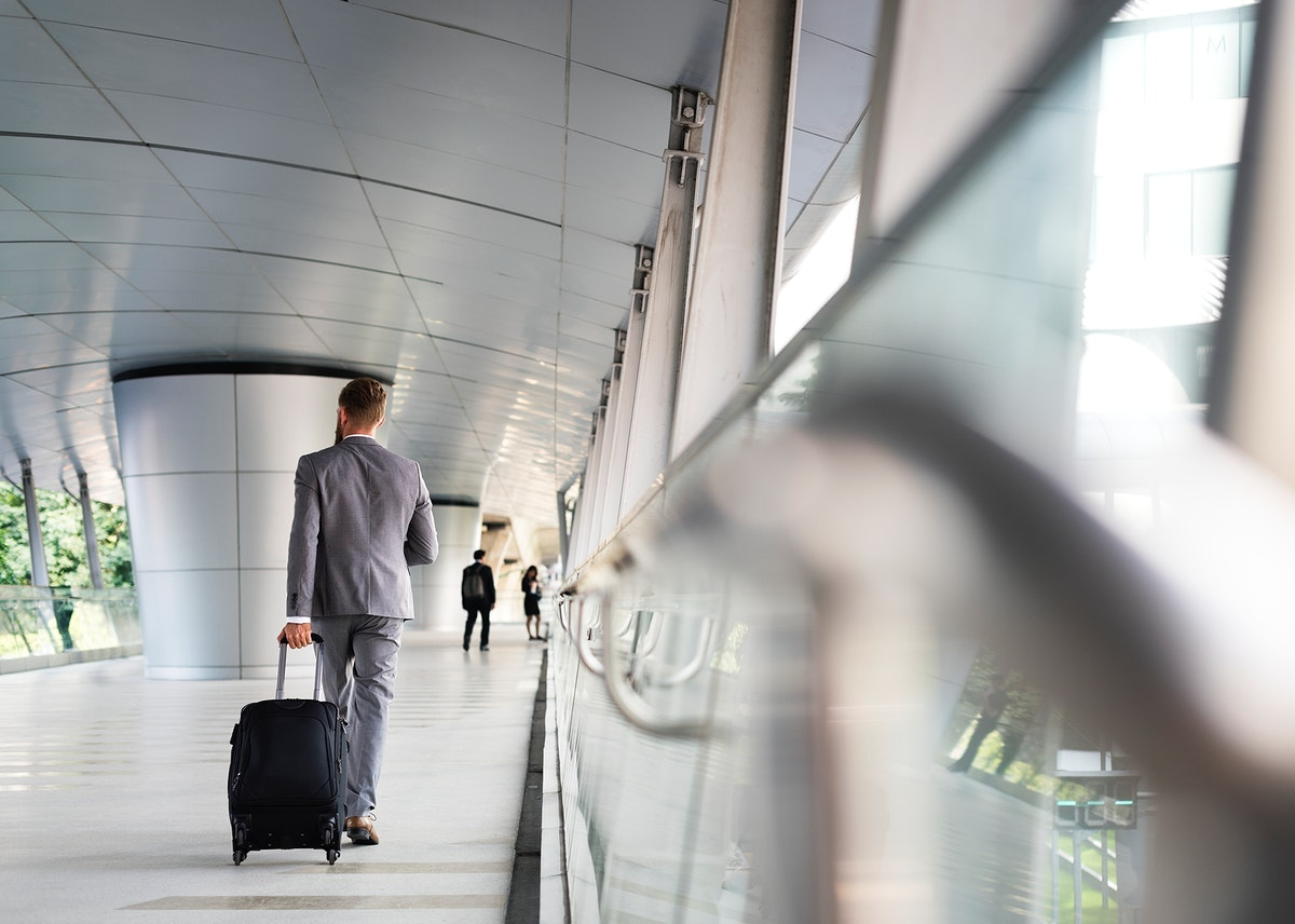 Businessman carrying a luggage while walking