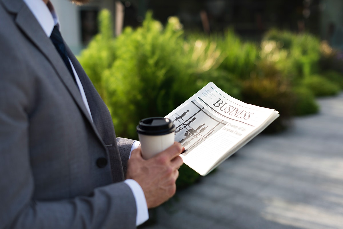 Businessman holding a cup of coffee and reading a newspaper