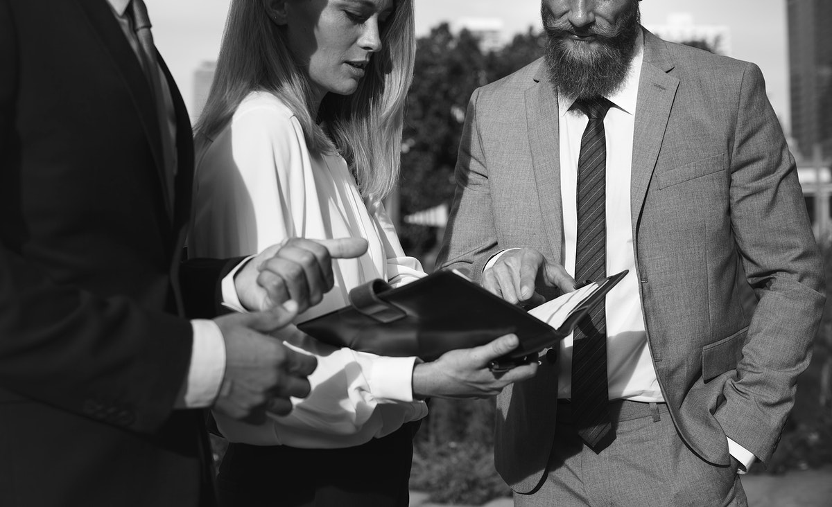 A businessman and a businesswoman pointing at a notebook and discussing